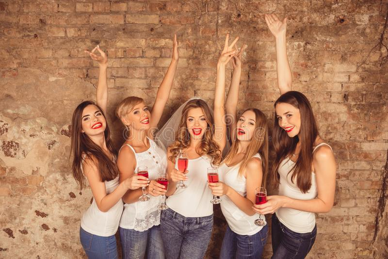 Cheerful bride and happy bridesmaids celebrating hen-party with red champagne.  royalty free stock photos