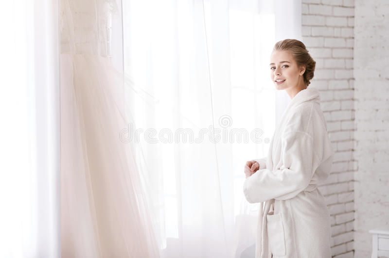 Cheerful bride standing near the window in the white room. The most exciting event of my life is coming. Delighted cheerful young bride standing in the white stock photography