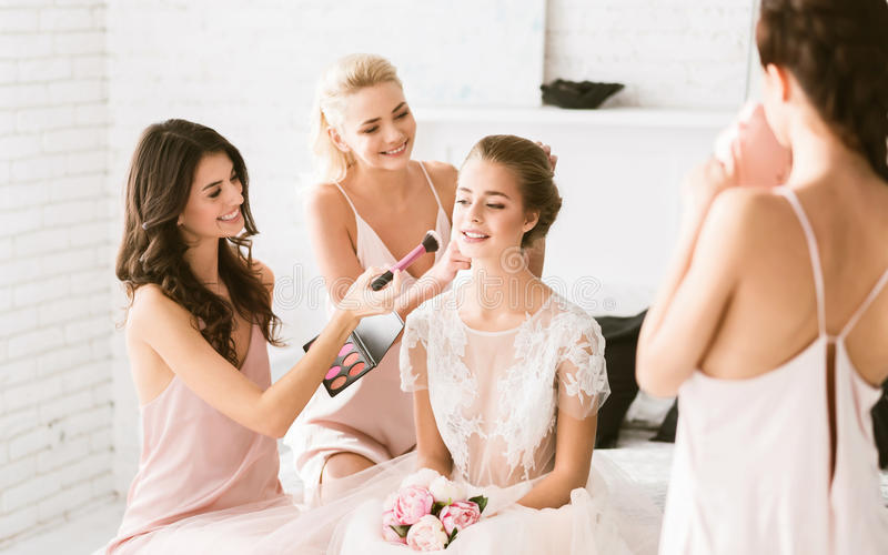 Cheerful bridesmaids preparing the young bride to the wedding ceremony royalty free stock photos