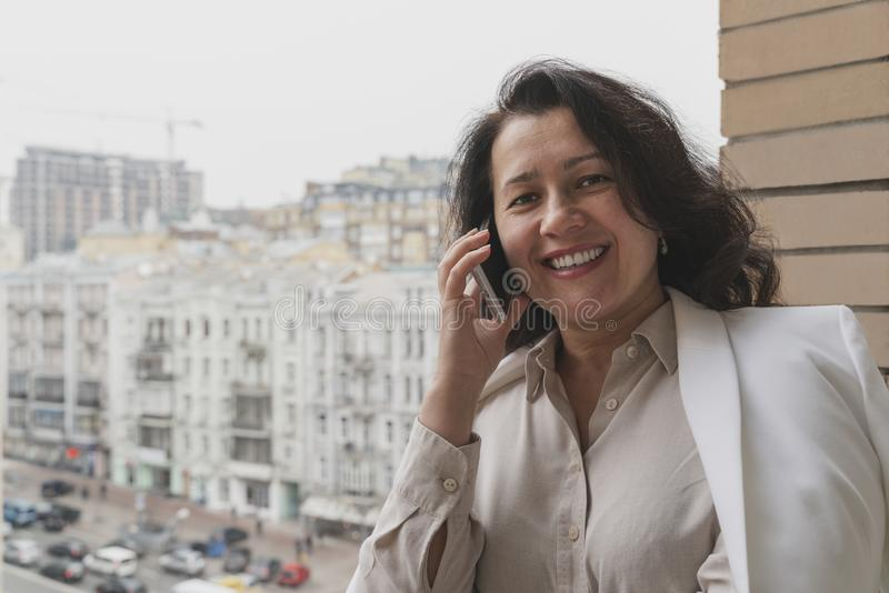 Cheerful brunette entrepreneur is talking on the phone on the balcony. Freelance and flexible hours working concept royalty free stock photography