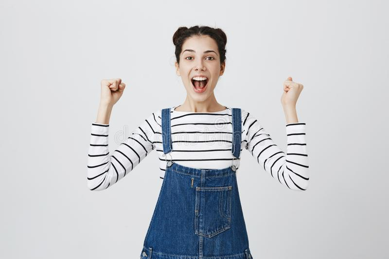 Cheerful brunette European female with hairbuns in denim overall excited and glad to achieve victory, clenches fists and royalty free stock image