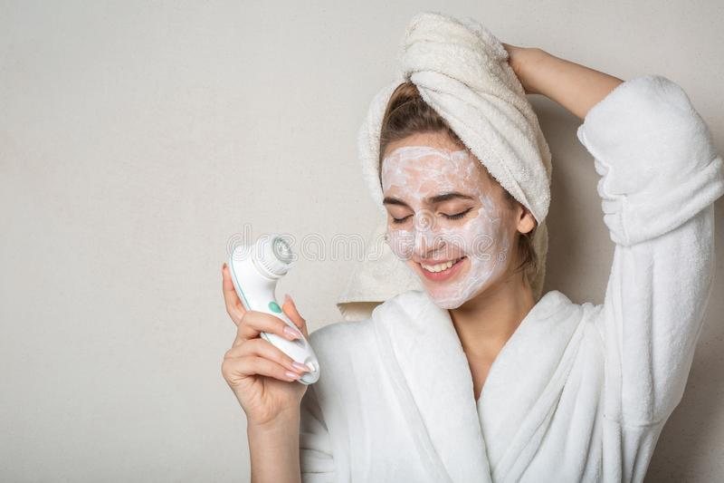 Cheerful brunette model posing with moisturizing cream mask and face cleaner. Empty space. Cheerful brunette woman posing with moisturizing cream mask and face royalty free stock images