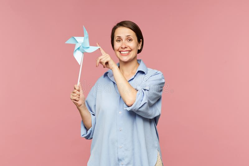 Cheerful brunette woman in blue shirt playing with paper whirligig royalty free stock photos
