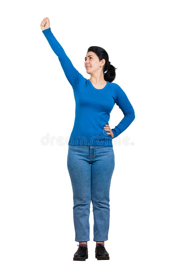 Cheerful brunette woman full length portrait raising arm as holding something imaginary, looking up confident. Brave girl gesture royalty free stock photography