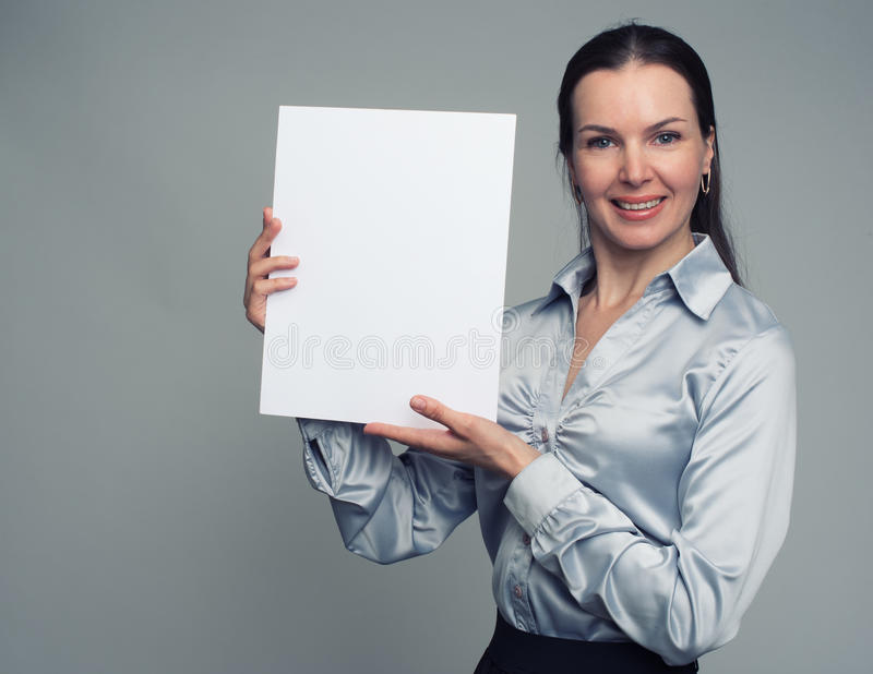 Cheerful brunette woman holding a white blank poster. Portrait of a cheerful young brunette woman holding a white blank poster royalty free stock photography