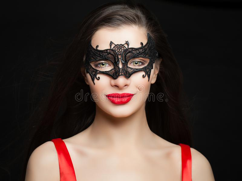Cheerful brunette woman with makeup and carnival mask on black background, Halloween concept royalty free stock photography