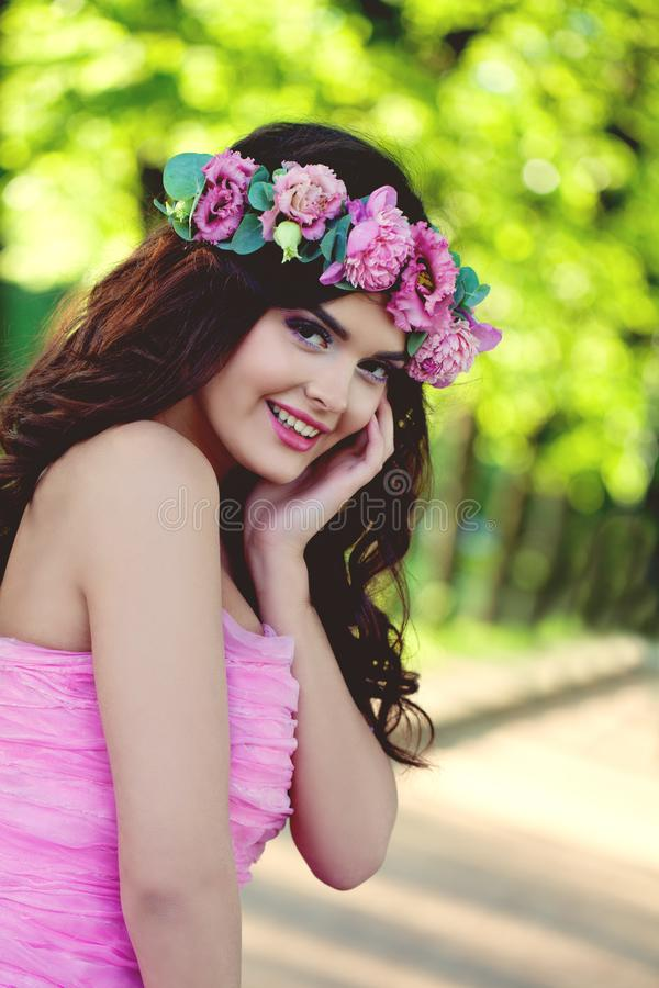 Cheerful brunette woman outdoors portrait. Smiling model with flowers royalty free stock images