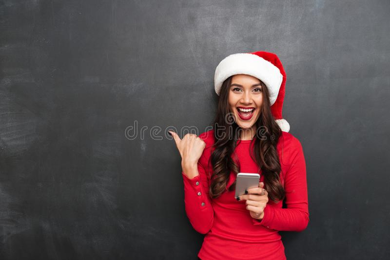 Cheerful brunette woman in red blouse and christmas hat royalty free stock photos