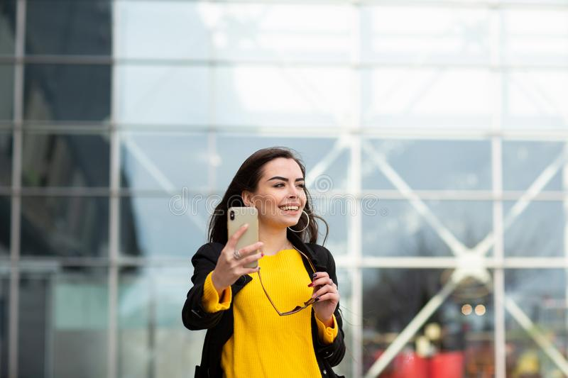 Cheerful brunette woman in yellow sweater making sefie against airport background. Modern technology.  stock photography