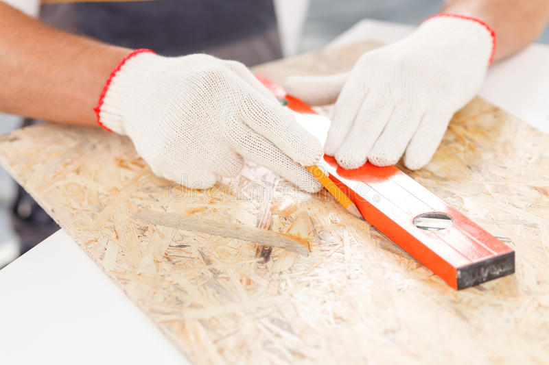 Cheerful builder is making measurements of wooden. Close up of arms of male carpenter measuring wood board with ruler. The man is holding pencil and drawing the royalty free stock images