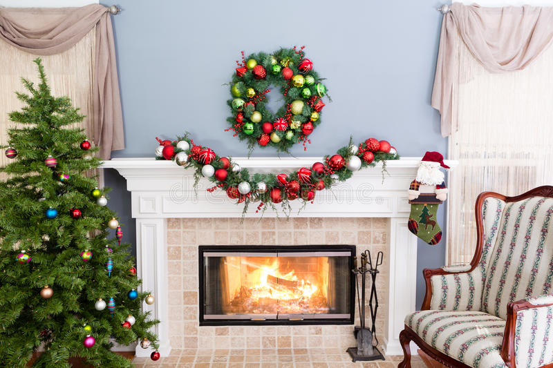 Cheerful burning fire in the hearth at Christmas. With a vintage sofa, decorated tree, wreath and garland of baubles decorating the mantelpiece royalty free stock image