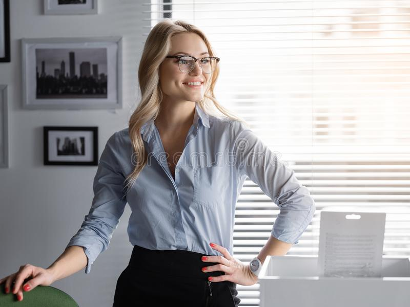 Cheerful business lady relaxing at her workplace stock photography