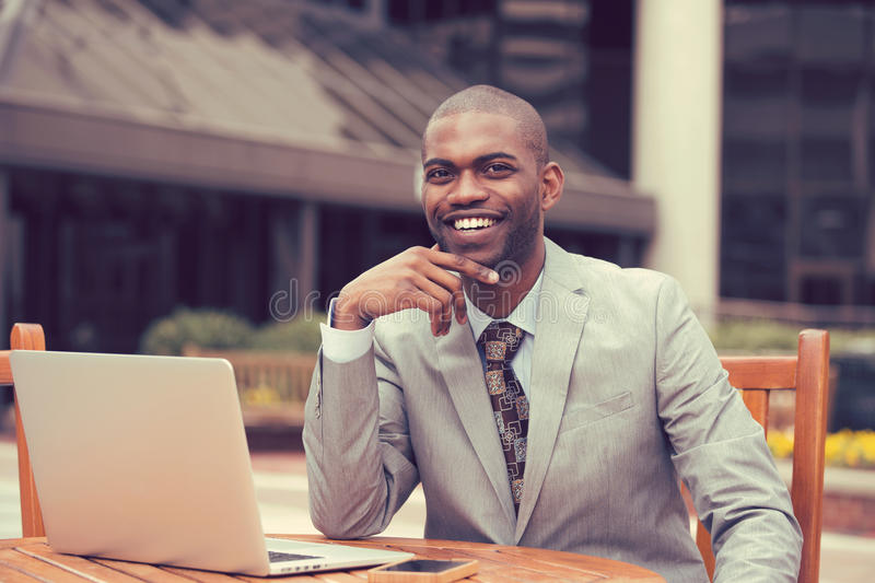 Cheerful business man sitting at table with laptop outside corporate office. Cheerful business man in a stylish suit sitting at table with laptop outside stock photography