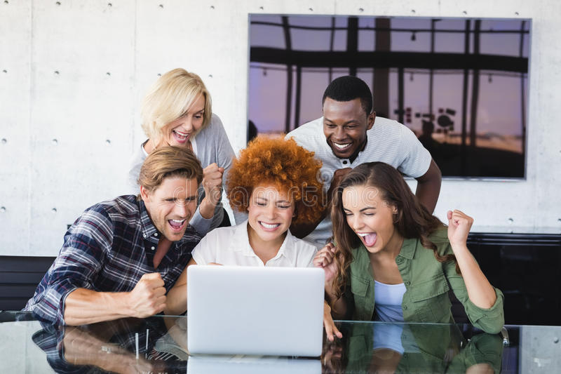 Cheerful business people looking at laptop royalty free stock images