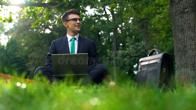 Cheerful business person working on laptop in forest, inspired by nature energy stock image