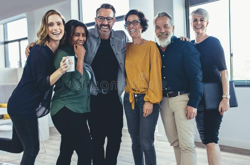 Cheerful business professionals. Cheerful business people standing together and laughing. Team of business professionals looking at camera and smiling royalty free stock photos