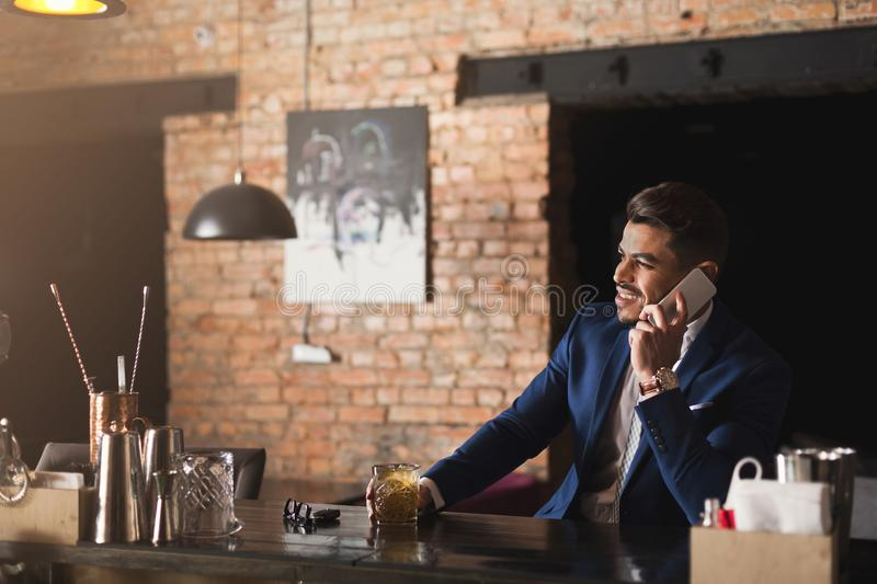 Cheerful business talking on phone in bar royalty free stock photo