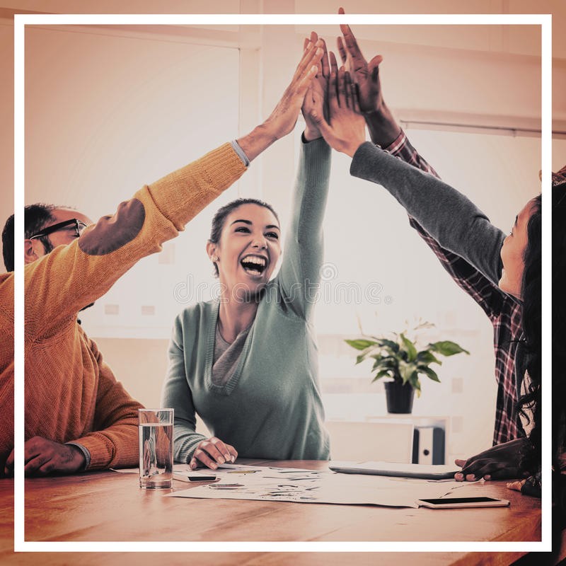 Cheerful business team doing high five in creative office royalty free stock image