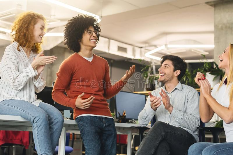 Cheerful business team greeting their successful colleague royalty free stock image