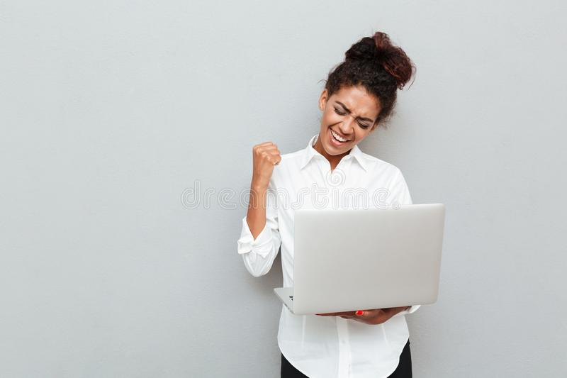 Cheerful business woman make winner gesture. royalty free stock photography