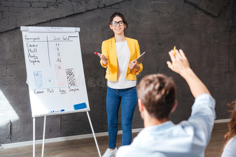 Cheerful business woman making presentation and answering questions of audience royalty free stock photography