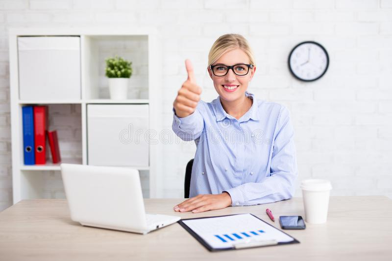 Cheerful business woman sitting in office and thumbs up stock image