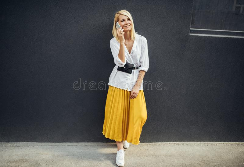 Cheerful business woman standing next to gray wall while talking on smart phone. Pretty student female wears casual and looking up. Horizontal shot of happy royalty free stock photo