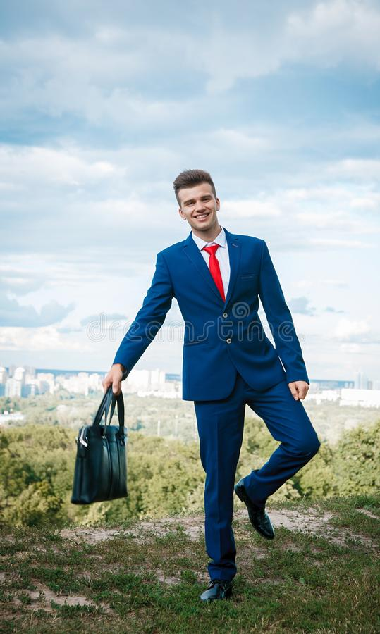 Cheerful businessman. Cheerful smiling businessman who made a good deal dressed in blue suit and red tie with a briefcase in his hand against the backdrop of the royalty free stock photography