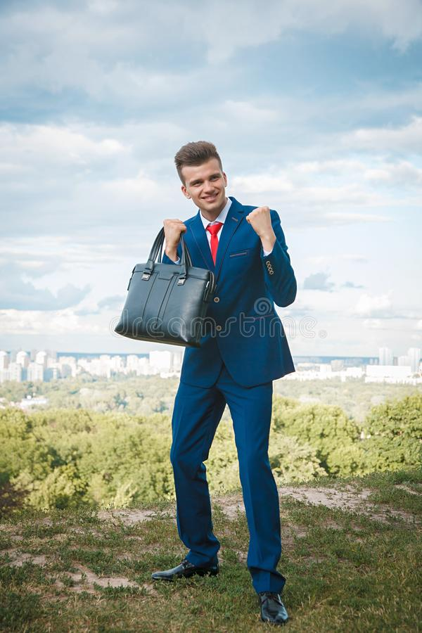 Cheerful businessman. Cheerful smiling businessman who made a good deal dressed in blue suit and red tie with a briefcase in his hand against the backdrop of the stock images