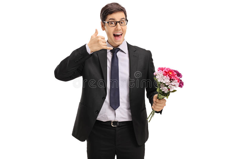 Cheerful businessman with flowers making a call me gesture. Isolated on white background royalty free stock photography