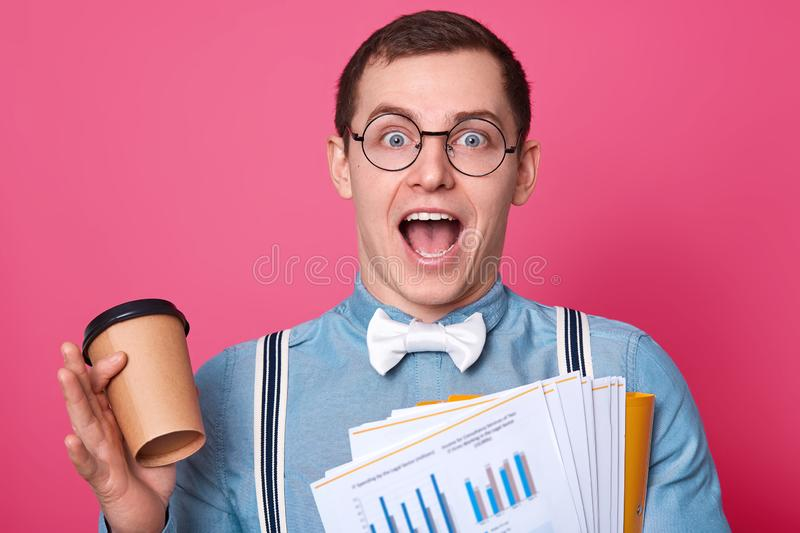 Cheerful businessman has great idea whil having resting and drinking coffee from paper cup. Handsom Caucasian guy wears blue shirt. And suspenders, stands stock image