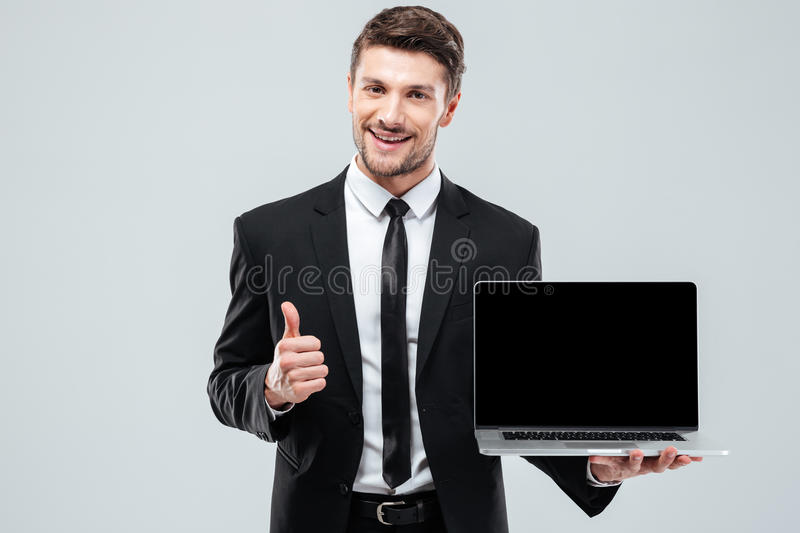 Cheerful businessman holding blank screen laptop and showing thumbs up. Cheerful young businessman holding blank screen laptop and showing thumbs up over white stock images