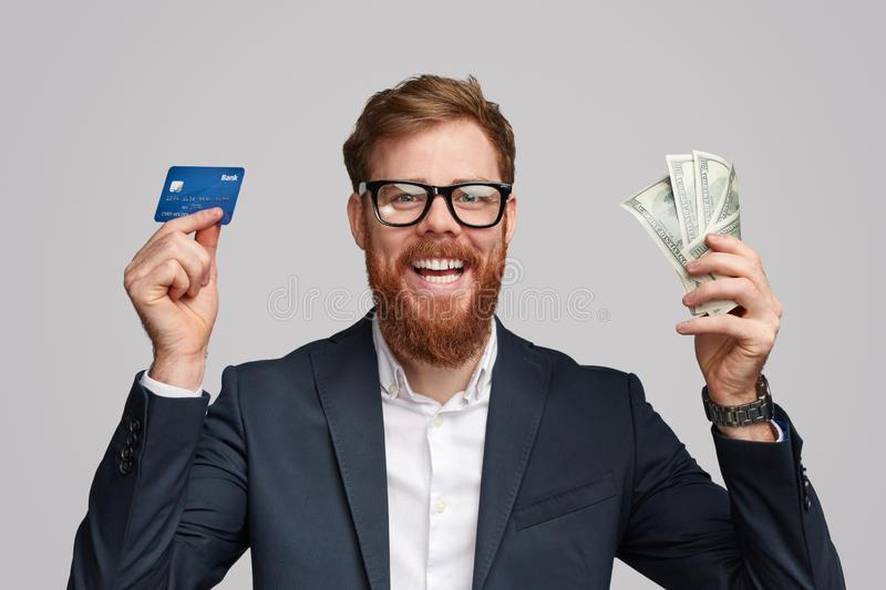 Cheerful businessman with money and bank card stock photo