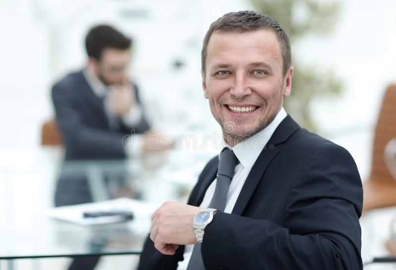 Cheerful businessman posing in the meeting room while colleagues royalty free stock image