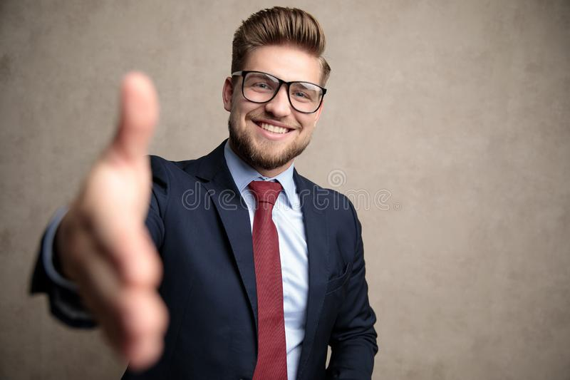 Cheerful businessman reaching for a handshake and smiling royalty free stock photos