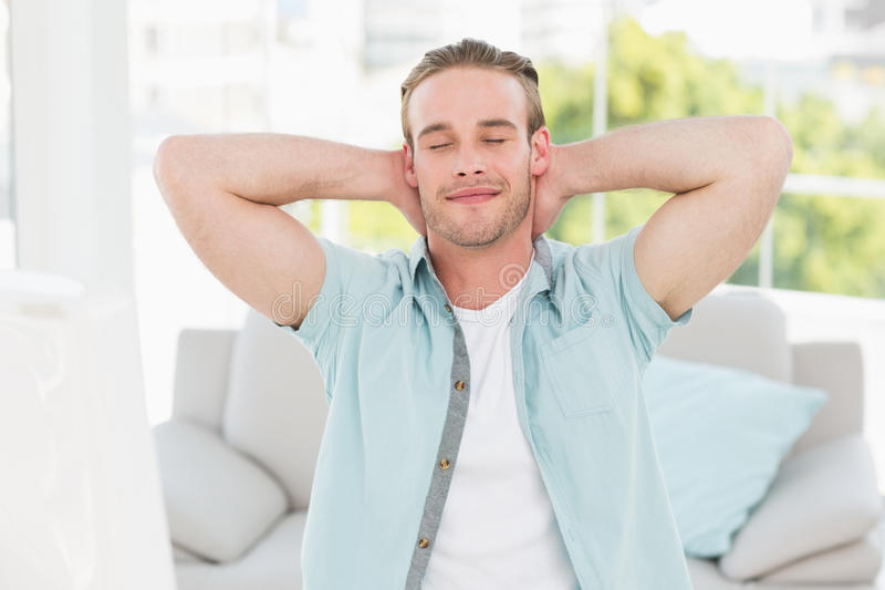 Cheerful businessman resting with hands behind head royalty free stock images