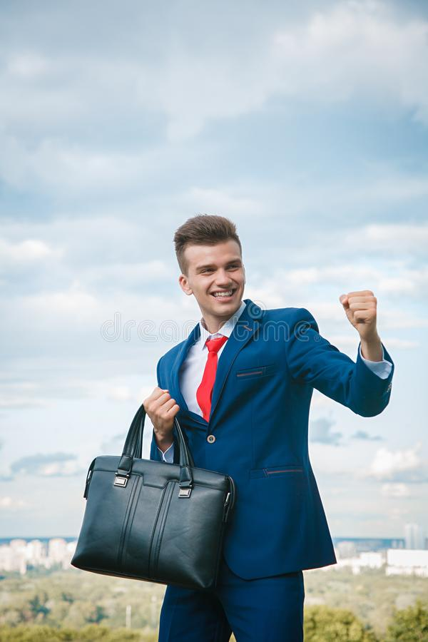 Cheerful businessman. Cheerful smiling businessman who made a good deal dressed in blue suit and red tie with a briefcase in his hand against the backdrop of the royalty free stock images