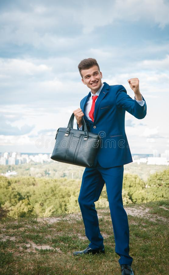 Cheerful businessman. Cheerful smiling businessman who made a good deal dressed in blue suit and red tie with a briefcase in his hand against the backdrop of the royalty free stock photo