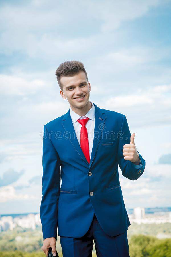 Cheerful businessman. Cheerful smiling businessman who made a good deal dressed in blue suit and red tie with a briefcase in his hand against the backdrop of the stock photography