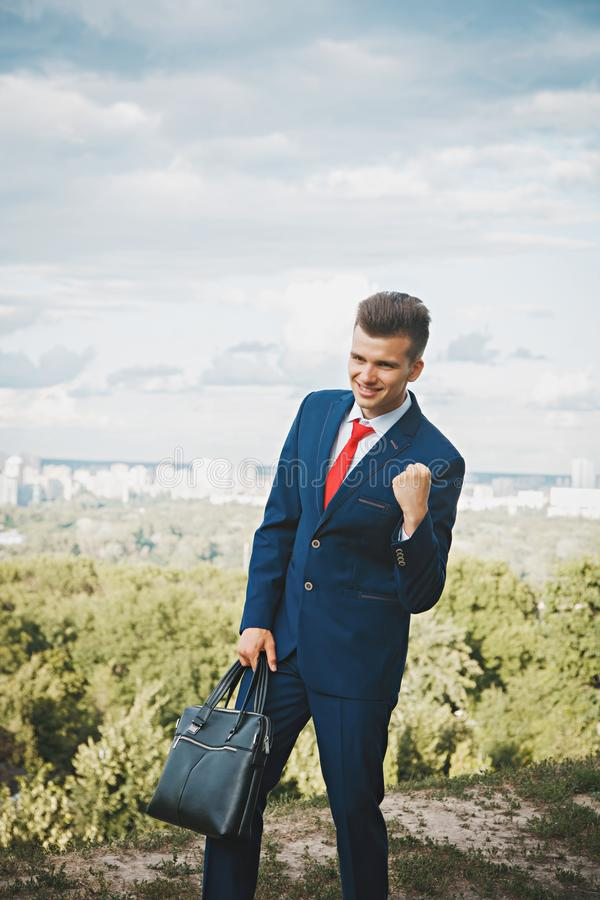 Cheerful businessman. Cheerful smiling businessman who made a good deal dressed in blue suit and red tie with a briefcase in his hand against the backdrop of the stock photo