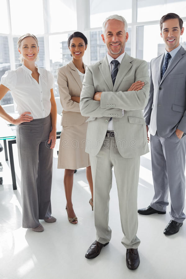 Cheerful businessman standing in front of colleagues stock photos