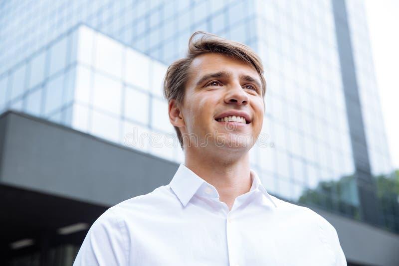 Cheerful businessman standing near modern skyscraper royalty free stock image