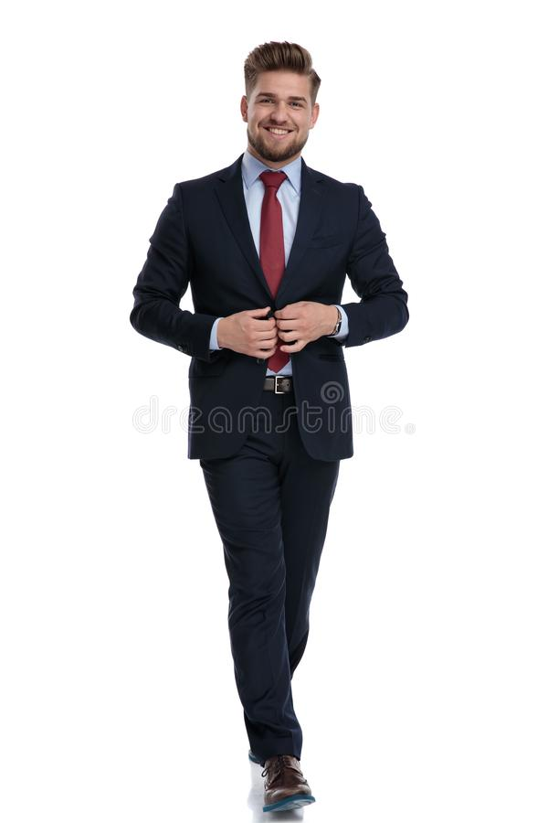 Cheerful businessman stepping and adjusting his jacket stock photography