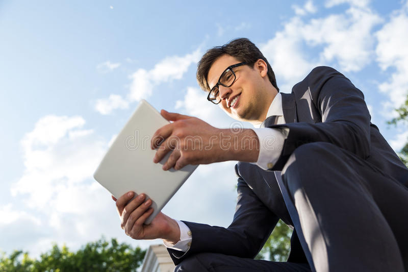 Cheerful businessman using tablet outside royalty free stock images