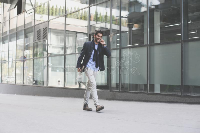 Businessman walking on street and holding iPod. Space f stock photos