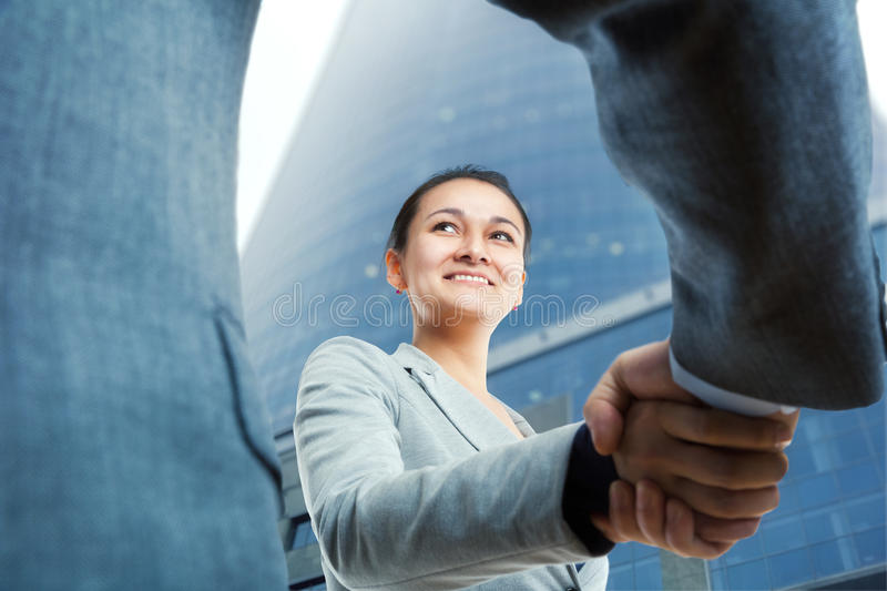 Cheerful businesswoman and client handshaking. Happy businesswoman and client handshaking royalty free stock image