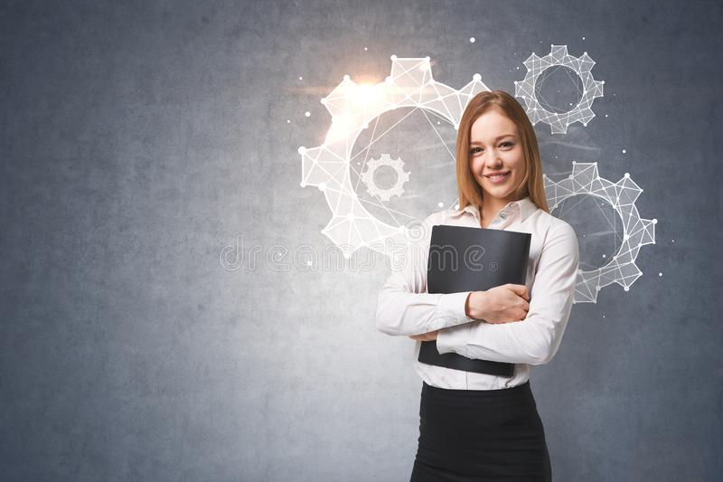 Cheerful businesswoman, cogwheels, gray wall. Smiling young businesswoman hugging a folder standing near a concrete wall with cogwheels and gears on it. Teamwork stock image