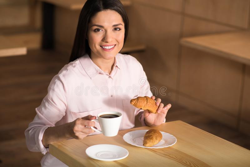 Businesswoman drinking coffee with croissants. Cheerful businesswoman drinking coffee with croissants in cafe and looking at camera stock photo