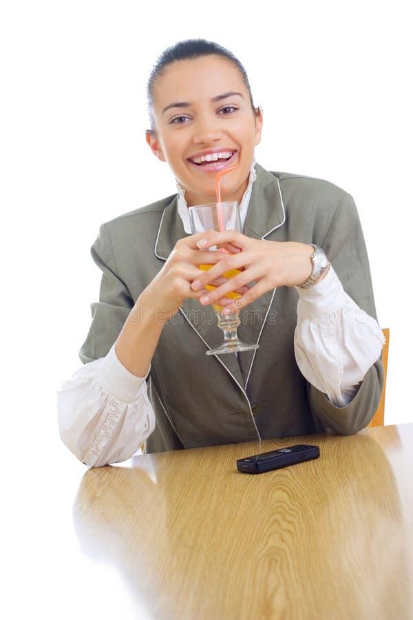 Cheerful businesswoman drinking juice