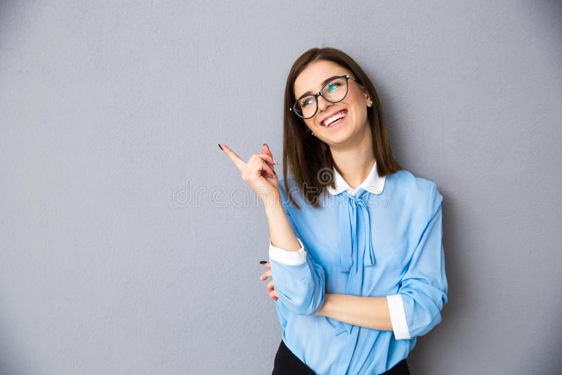 Cheerful businesswoman in glasses pointing away royalty free stock photos